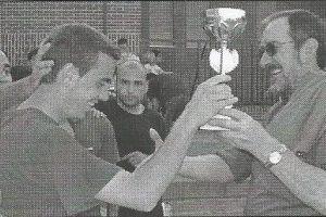 Nuestro joven feligrés Pablo Berrocal recibe el trofeo del equipo campeón de manos del padre José Antonio.